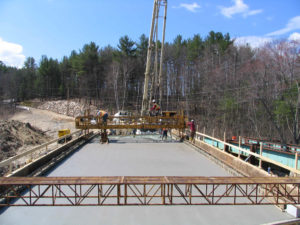 Construction workers placing concrete on Berry Road Bridge in Alexandria, NH